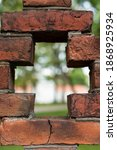 Small photo of Red brick outer perimeter wall with perforated cross design holes and blurred background view inside the perimeter