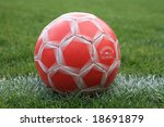 Weathered Red Soccer Ball on the Field - stock photo