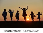 Happy children silhouettes on summer meadow running and jumping - stock photo