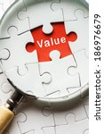 """Small photo of Magnifying glass searching missing puzzle peace """"VALUE"""""""