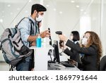Small photo of Male traveler shows phone to female officer at airline check in counter for issue airplane ticket boarding pass. Woman staff wear face mask to prevent from coronavirus pandemic. New normal lifestyle