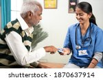 Small photo of Selective focus on girl, Concept of home health visit or service - doctor or nurse checking pulse using pulse oximeter of sick senior man while both worn face mask