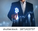 Small photo of Businessman pointing digital bitcoin icon. Increase in value of cryptocurrencies. Futuristic stock exchange. Concept of the rise in prices for bitcoin.