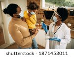 Small photo of African American father and daughter talking to their family doctor who is visiting them at home during coronavirus pandemic. Focus is on doctor.