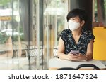 Small photo of A beautiful asian female wearing face mask in a cafe, absent-minded looking out the window with smartphone in her hands. New normal, Social distancing, Covid19, Pandemic fatigue, Global economy crisis