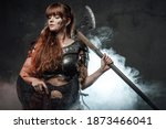 Small photo of Violent and warlike northern woman warrior holding axes and posing in dark smokey background.