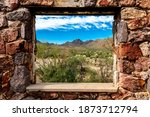 Looking through the window at the picturesque desert landscape from the ruins of a stone house on the Bowen Trail in Tucson Arizona.