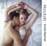 young lovers lay in bed   only... | Shutterstock . vector #187371764
