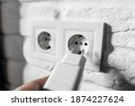 Small photo of Unplugging idle appliances saves electricity. Idle phone chargers or power adapters. Vampire power, standby power. Plug-in adapter into european wall outlet. USB plug insert into electric wall socket