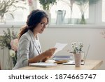 Small photo of Important message. Focused attentive young woman florist designer sitting at work desk in office studio. Small business owner involved in reading paper letter from bank of credit loan terms conditions