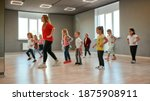 Small photo of Group of little boys and girls dancing while having choreography class in the dance studio. Female dance teacher and children. Contemp dance. Hip hop. Kids and sport. Full length