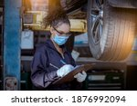 Small photo of Car mechanic under checking car wheels at garage for maintenance or charge a new new wheel ,they wearing safety uniform, glasses and face mask to work.