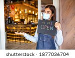 Small photo of Happy female waitress with protective face mask holding open sign while standing at cafe or restaurant doorway, open again after lock down due to outbreak of coronavirus covid-19