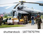 Small photo of Kathmandu, Nepal - April 29, 2015: Nepali Army personnel unload relief material for earthquake affected people from a Indian Airforce Mil Mi-17 helicopter at Tribhuvan International Airport.