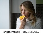 Small photo of Sick woman trying to sense smell of half fresh orange, has symptoms of Covid-19, corona virus infection - loss of smell and taste. One of the main signs of the disease.