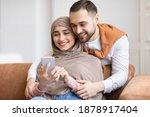 Happy Muslim Couple Using...