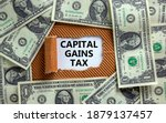 Small photo of Capital gains tax symbol. The text 'Capital gains tax' appearing behind torn brown paper. Dollar bills. Business and capital gains tax concept.