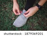 A Woman Tie Shoelaces On Grass...