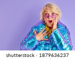 Small photo of amazed surprised lady smiling, stand ins hock holding chest, with wide opened mouth, in sunglasses, isolated over purple background