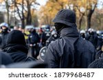 Anonymous masked left wing antifa, or so called black block is standing in front of a riot police line with helmets on in Germany to block other protesters.