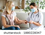 Small photo of Homehealth care. Woman nurse in a medical mask help middle aged woman during during illness or pressure, female doctor measures the patient's pulse and oxygen saturation using a pulse oximeter