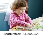 Stock photo cute baby girl or toddler playing with a puzzle child development concept 188023364