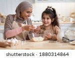 Small photo of Happy islamic mom and her cute daughter preparing dough in kitchen together, cracking eggs to bowl, enjoying cooking homemade food, little girl and her muslim mother in hijab having fun at home