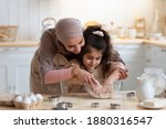 Small photo of Loving Muslim Mom Teaching Daughter How To Knead Dough, Having Fun Together In Kitchen At Home, Woman In Hijab Helping To Her Little Child, Islamic Family Enjoying Making Homemade Pastry, Free Space