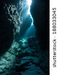 Small photo of Sunlight penetrates the sea and illuminates a dark crevice at a dive site known as Yap Caverns. Dark habitats such as this provide homes to many shade-loving marine species.