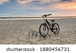 Bicycle at sandy beach of the Baltic Sea during sunset