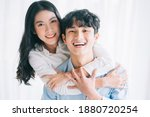 Asian Couple Happily Embracing...