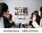 Small photo of Business meeting.A group of formal successful people wearing protective masks sit at the table and communicate online via videoconference with colleagues discussing about important business strategies