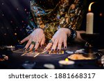 Small photo of Cartomancy. A fortune teller reads Tarot cards. On the table are candles and fortune-telling objects and sparks. Hands close up. The concept of divination, astrology and esotericism