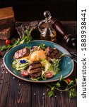 Small photo of Eggs benedict with beef meat on a large white plate.. Traditional english breakfast with eggs Benedict, cherry tomato, lettuce. Benedict egg served on restaurant table background.
