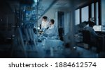 Small photo of Modern Medical Research Laboratory: Two Scientists Working, Using Digital Tablet, Analyzing Test, Talking. Advanced Scientific Pharmaceutical Lab for Medicine, Biotechnology Development. Evening Time