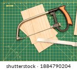 Small photo of Wood saw on green cutting board with balsa wood pieces.