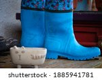 Small photo of Old dirty rubber boots stand on the wooden floor of a country house porch. Blue rubber country goloshes.