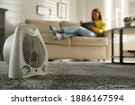 Small photo of Woman reading book in living room, focus on electric fan heater