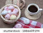 Small photo of Homemade meringue kisses and coffee cup. Meringue cookies in wicker basket on natural sackcloth background
