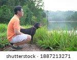 Dog Facing Foggy Lake Together...