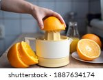 Small photo of Female hand squeezing orange juice from fresh oranges with a juicer in the home kitchen, ?lose up.
