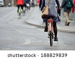 Small photo of Woman on bike in light rain on her way home from work