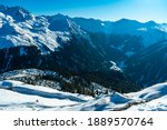 Snow drift in the winter wonderland of the Vorarlberg Alps, with fir trees and snow hollows, mountains in the background and a wonderful blue sky. snowy Austrian mountains with interesting formations
