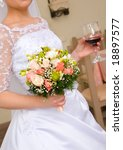 bride with a wedding bouquet and glass of red wine - stock photo