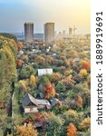 Small photo of Contemporary highrise city dwelling buildings annex territory of neat summer cottages among colorful autumn trees at sunset