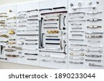 Small photo of Big selection of handles cabinets parts on a white background shop window. samples of Metal and Stainless Steel handle styles on wooden kitchen cabinet with different Stainless Steel handles.
