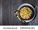 Small photo of Crab salad of artificial crab meat with vegetables: corn, cucumbers, scallion, hard-boiled eggs, jasmine rice served in a black plate on a dark wooden table, top view, close-up, copy space