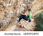 young female rock climber on a...