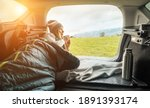 Small photo of Girl resting in her car. Woman hiker, hiking backpacker traveler camper in sleeping bag, drinking hot tea and relaxing on top of mountain. Health care, authenticity, sense of balance and calmness.