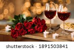 Small photo of Romantic Dinner. Bouquet of flowers lying on the table, selective focus on bunch of roses, two glasses of red wine and candles on the wooden desk. Date concept, blurred background, banner, copy space